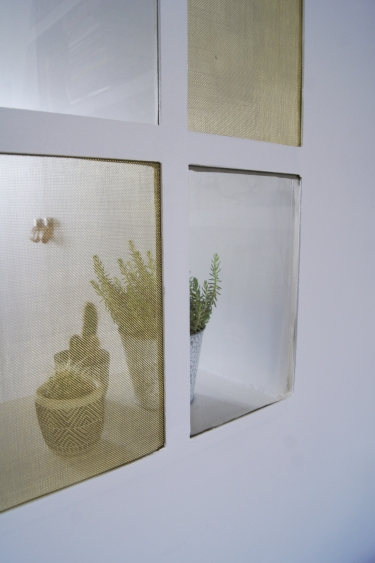 Derrière la verrière, le verre et le laiton laissent voir les succulantes.