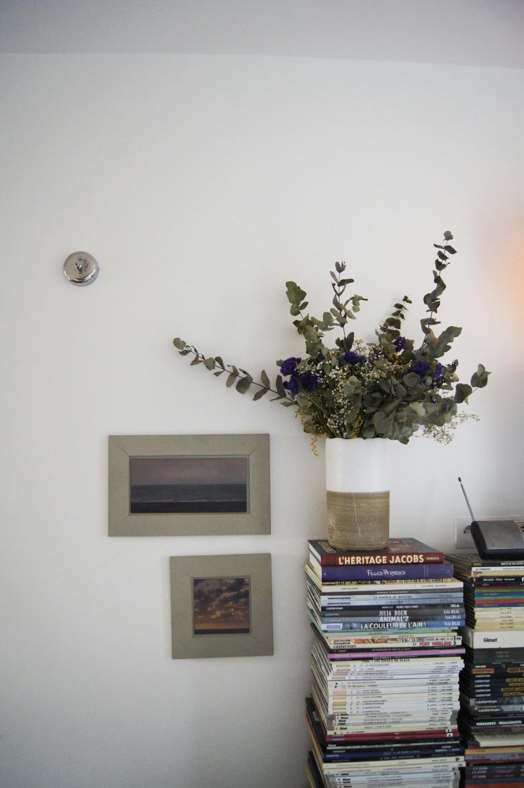 Garance dispose d'une énorme collection de BD. Pour ne pas recouvrir la totalité de l'appartement de rayonnage de bibliothèque jusqu'au plafond, on a choisi de les empiler en pied de lit. Les tableaux sont de l'artiste Reynal Goldstein et représentent la Baie de Somme.