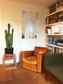 Nous avons créé une verrière entre la chambre et le salon. Comme on voulait éviter la verrière noire verticale, on a imaginé un design début du vingtième, que nous avons twisté en glissant sous le verre, un grillage de laiton. Les tables gigognes viennent de chez Habitat.